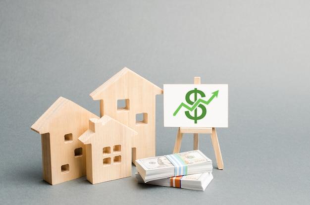 Figuras de madeira de casas e um cartaz com dinheiro