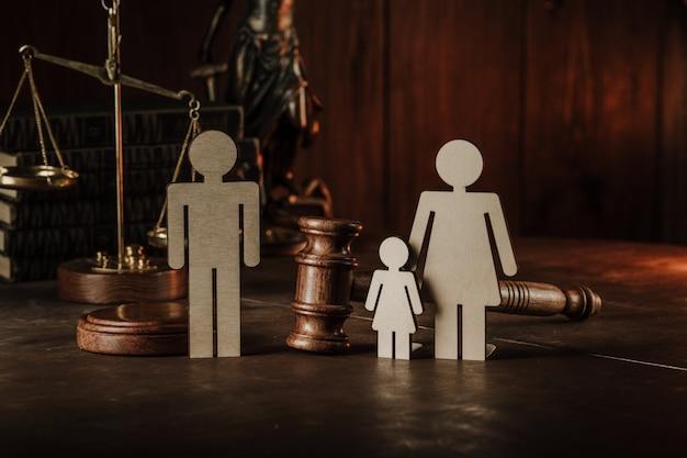 Figuras de madeira de família com criança e martelo sobre uma mesa