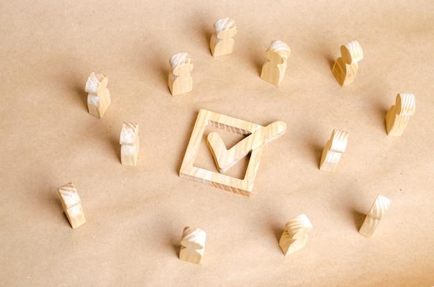 Figuras de madeira de pessoas cercam a caixa de seleção com um carrapato. o conceito de eleições