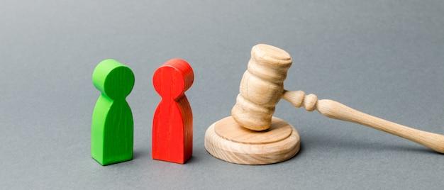 Figuras de madeira de pessoas em pé perto do martelo do juiz. litígio. rivais de negócios.