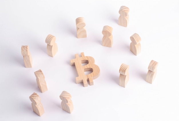 Figuras de madeira de pessoas estão de pé perto de um bitcoin em um fundo branco
