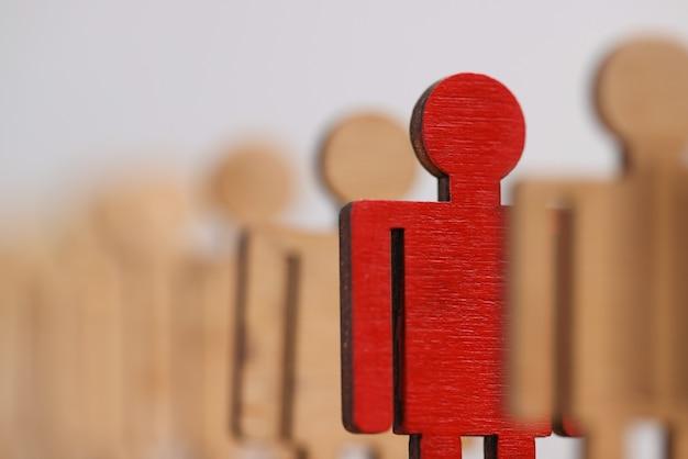 Figuras de madeira de pessoas, uma delas é vermelha