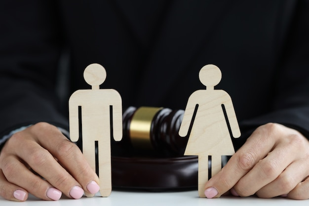 Figuras de madeira de um homem e uma mulher nas mãos do juiz no contexto do conceito de martelo do juiz
