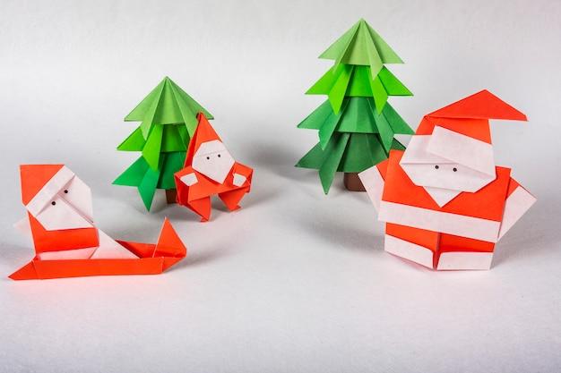 Figuras de origami artesanal de cartão de ano novo. natal conceito inverno trabalhada decorações tiro estúdio isolado papai noel origami