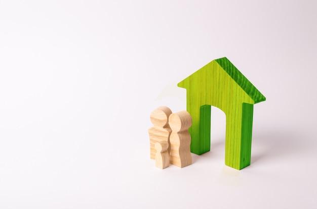 Figuras de pessoas estão perto de uma casa de madeira. uma jovem família está de pé perto da casa deles.