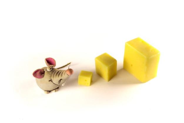 Figuras de ratos e um pedaço de queijo no fundo branco. estatueta de rato, close-up. conceito de ano novo. foco seletivo.