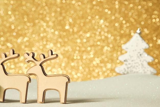 Figuras de renas de madeira em um fundo dourado brilhante em uma superfície branca brilhante com uma árvore de natal de fundo branco