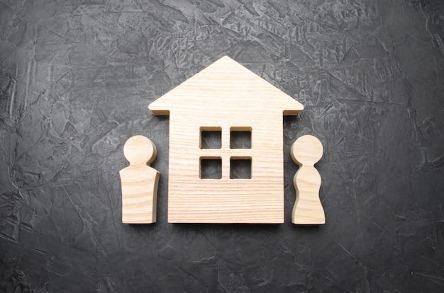 Figuras de um homem e uma mulher ficar perto de uma casa de madeira. marido e mulher perto de sua casa.