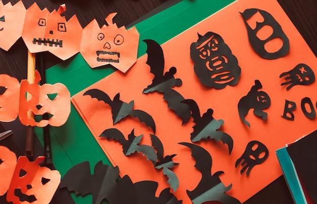 Figuras de um morcego preto e fantasmas, uma guirlanda de abóboras com rostos