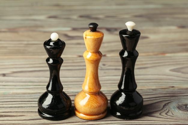 Figuras de xadrez na vista lateral para o fundo escuro de madeira copiam o espaço