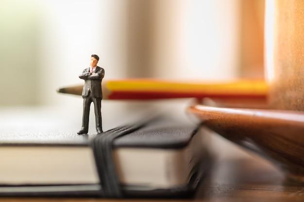 Figuras diminutas do homem de negócios que estão no caderno com o lápis com xícara de café.