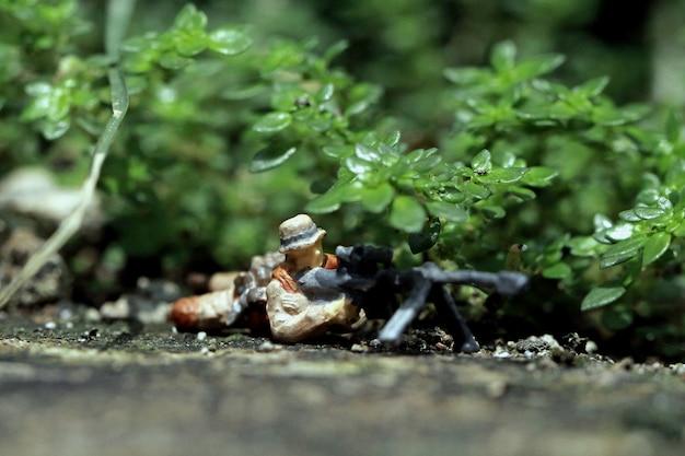Figuras em miniatura atirador furtivo escondido na pequena folha
