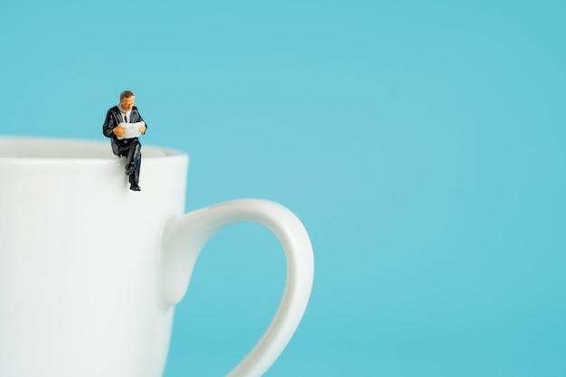 Figuras em miniatura de negócios sentado e ler um livro, ler jornal, esperando, conversando e relaxar na xícara branca de café quente.