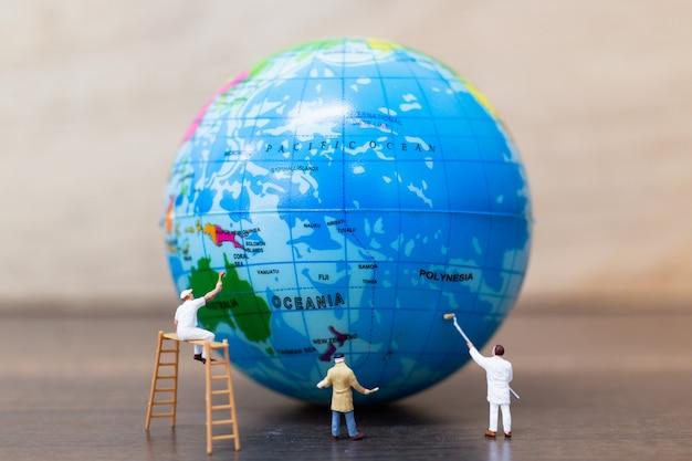 Figuras em miniatura de pintores estão pintando o globo