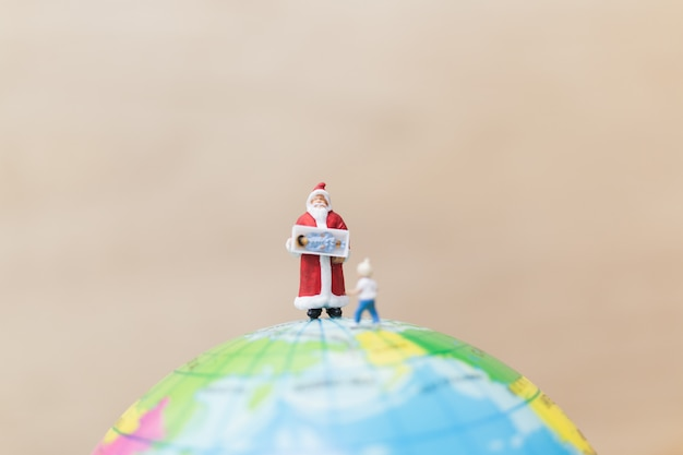 Figuras em miniatura do papai noel segurando o presente