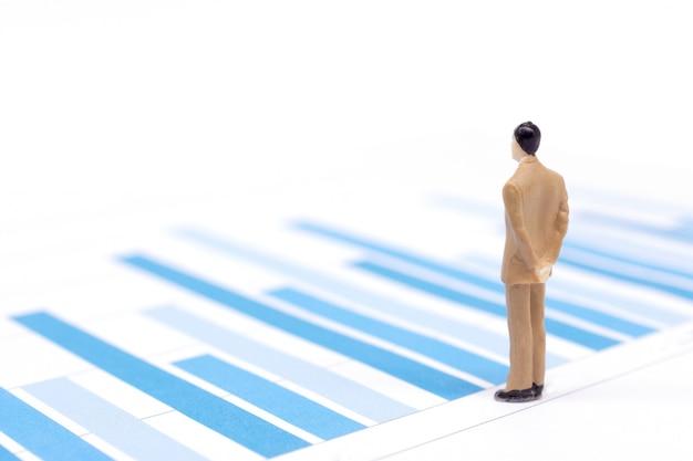 Figuras em miniatura empresários em pé em um gráfico gráfico financeiro