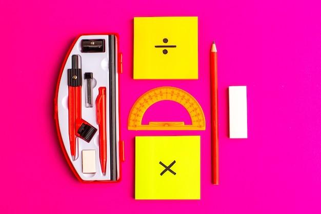 Figuras geométricas de vista frontal com lápis e adesivos na superfície roxa