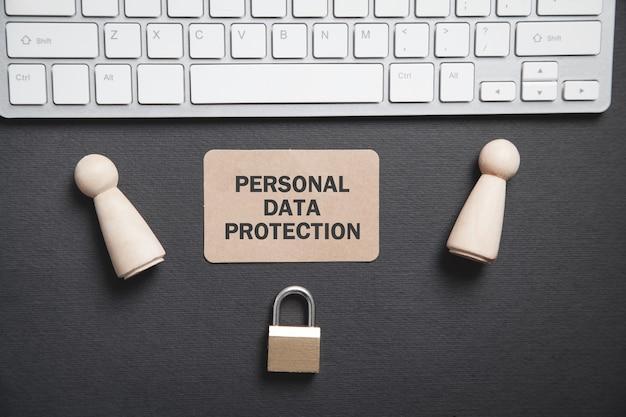 Figuras humanas de madeira, cadeado, teclado de computador. proteção de dados pessoais