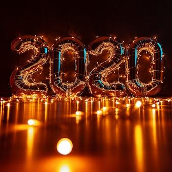 Figuras infláveis volumosas 2020 contra uma parede escura, envoltas em luzes de natal com lindos destaques e um lugar para texto