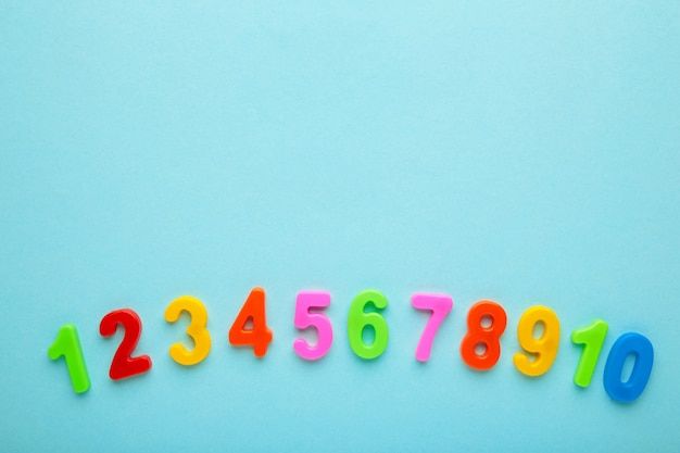 Figuras magnéticas multicoloridas sobre fundo azul com espaço de cópia. de volta à escola.