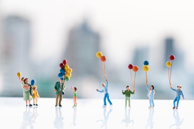 Figuras pequenas das crianças que prendem o balão com fundos da cidade.