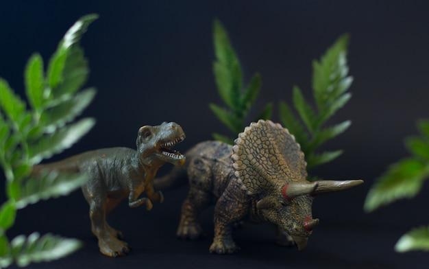 Figuras realistas dos dinossauros tiranossauro e triceratops sob suculentas folhas verdes