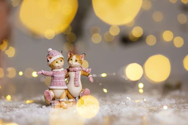 Figurinhas decorativas de gatos fofos abraçando, vestidas com uma camisola de malha