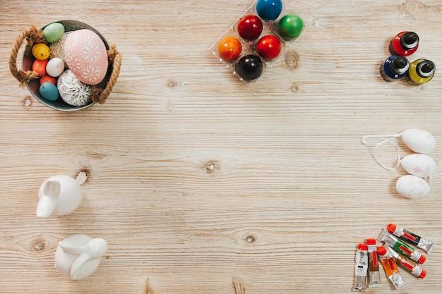Figurinhas e ovos com tintas na mesa
