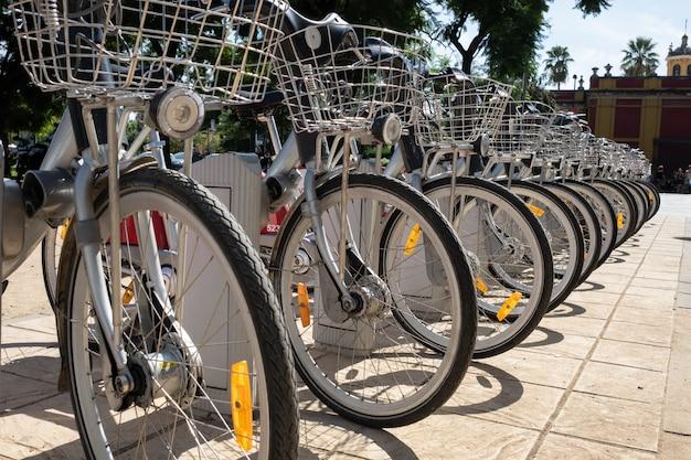 Fila de bicicletas com cesto estacionado na rua