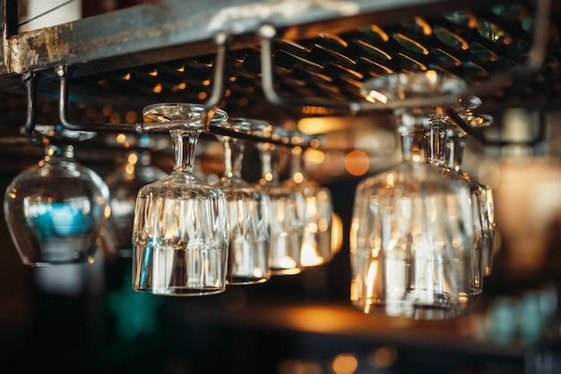 Fila de copos pendurada no balcão do bar, close-up