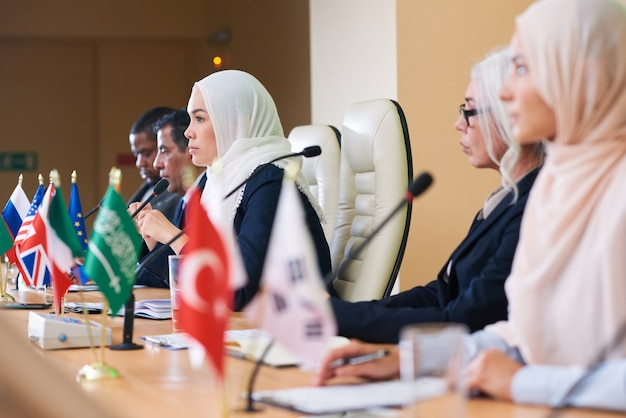 Fila de delegados interculturais sérios ouvindo atentamente um dos oradores estrangeiros na sala de conferências durante a cúpula