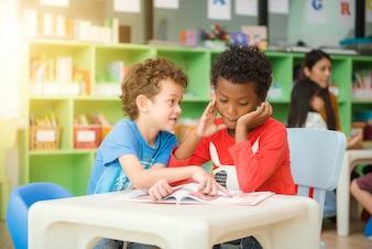 Fila de estudantes de ensino fundamental multiétnico lendo livro na sala de aula. Imagens de estilo de efeito vintage.