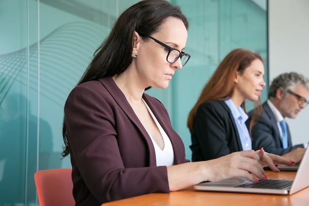 Fila de executivos sérios usando laptops, sentados em uma mesa e digitando