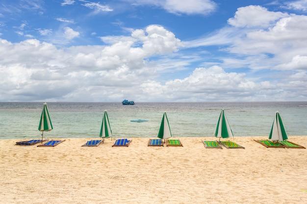Fila de guarda-sóis na praia com nuvens brancas em um céu azul