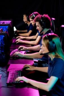 Fila de jovens jogadores de videogame contemporâneos com fones de ouvido sentados ao lado de uma mesa comprida em frente a monitores de computador durante a competição cibernética