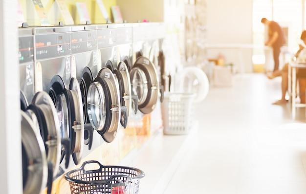 Fila de máquinas de lavar roupa industrial na lavanderia em uma lavanderia pública, com lavanderia em uma cesta, tailândia