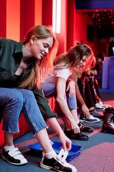 Fila de meninas e seus namorados calçando calçados enquanto se sentam no banco e vão jogar boliche no clube de entretenimento