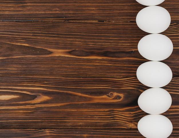 Fila de ovos brancos na mesa de madeira