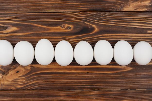 Fila de ovos de galinha branca na mesa de madeira