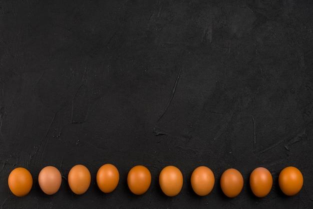 Fila de ovos de galinha marrom na mesa
