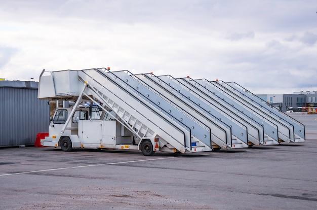 Fila de passarelas para embarque e desembarque de passageiros de um avião estacionado no aeroporto.
