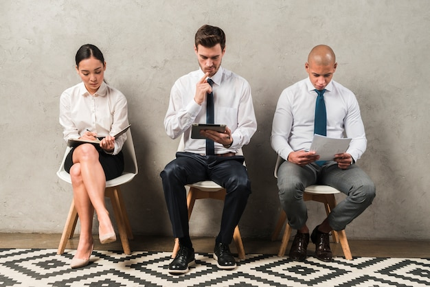 Fila, de, pessoas jovens, sentando, por, parede, enquanto, esperando, para, seu, volta, para, entrevista
