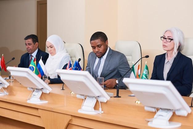 Fila de políticos interculturais contemporâneos jovens e maduros participando de fórum na sala de conferências