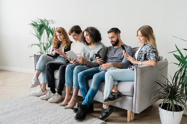 Fila de rapazes e moças casuais contemporâneos em trajes casuais, usando aparelhos modernos enquanto relaxam em grandes sofás