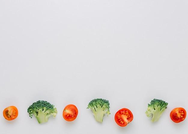 Fila de tomates-cereja cortados ao meio e brócolis verde na parte inferior em pano de fundo branco