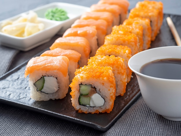 Filadélfia e califórnia rolam em uma placa escura texturizada. ao lado do molho de soja, wasabi e gengibre. vista lateral, close-up. culinária japonesa