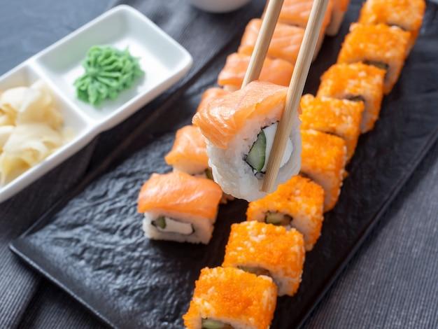 Filadélfia e califórnia rolam em uma placa escura texturizada. um rolo é segurado em palitos de vovó acima dos outros. ao lado do wasabi e do gengibre. vista lateral. culinária japonesa