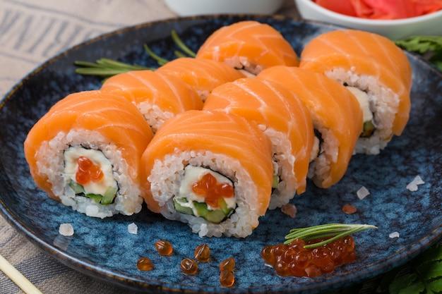 Filadélfia rola com salmão, abacate, caviar de peixe voador e cream cheese dentro de um prato azul.