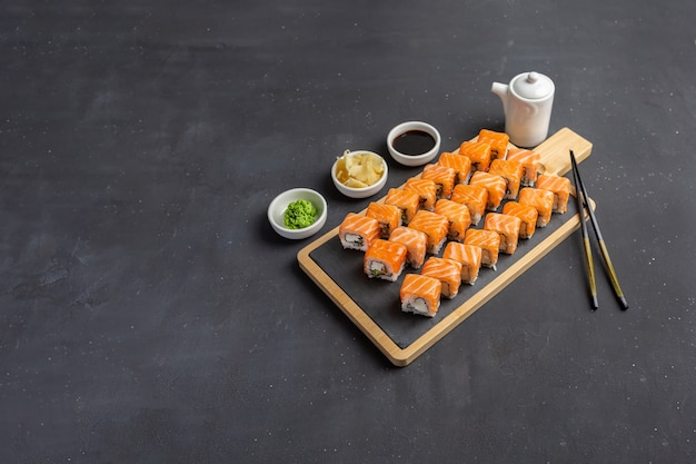 Filadélfia rola pedra escura clássica no tabuleiro. salmão, queijo philadelphia, pepino, abacate. sushi japonês. copie o espaço