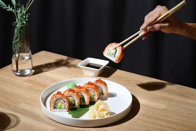 Filadélfia rolo no prato com wasabi e gengibre, mulher segura no pauzinho. rolo da filadélfia queimado.